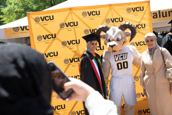 A yellow backdrop with the VCU logo and a daughter and father posing with Rodney the Ram