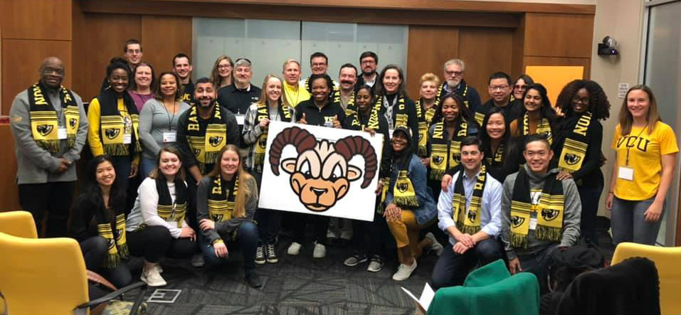 Group of volunteers wearing black and gold and holding an image of Rodney the Ra