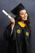 A girl in graduation regalia smiles while holding a diploma.